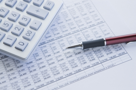 financial balance sheet with calculator and pen
