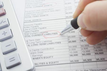 financial balance sheet with calculator and pen