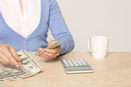 payable: desk with cash, calculator,  and coffee cup