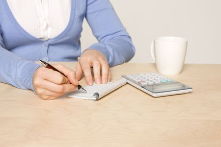 payable: woman sitting at desk with , calculator, checkbook, pen and coffee cup