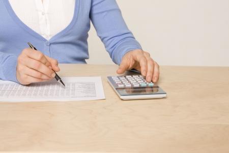 ledger: woman sitting at desk reviewing balance sheet Stock Photo