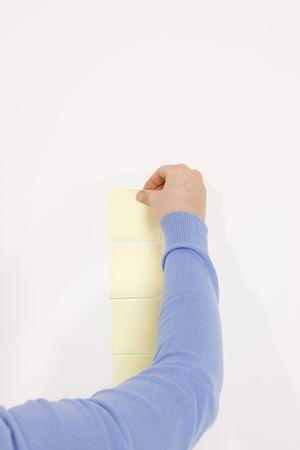 woman finishing column of reminder notes