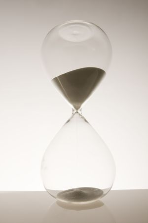 Hourglass on white background with ominous shadow  Stock Photo