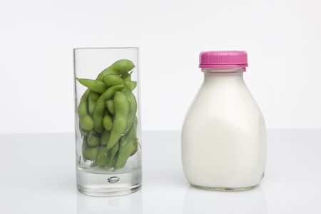 glass of soybeans next to glass jar of milk