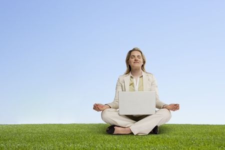 professional woman with laptop seated in zen position hovering over grass