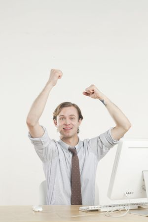 young professional at desk with hands in the air