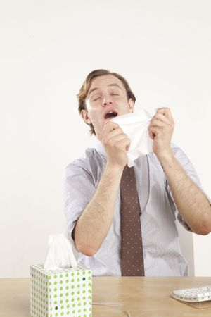 professional sitting at desk sneezing into tissue