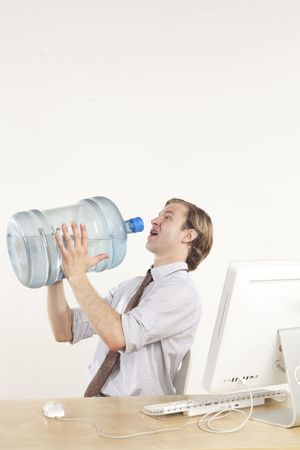 professional man sitting at desk drinking from giant water jug  Stock Photo