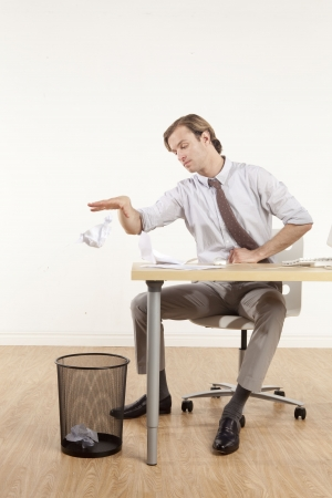 professional man sitting at desk throwing papers in wastebasket