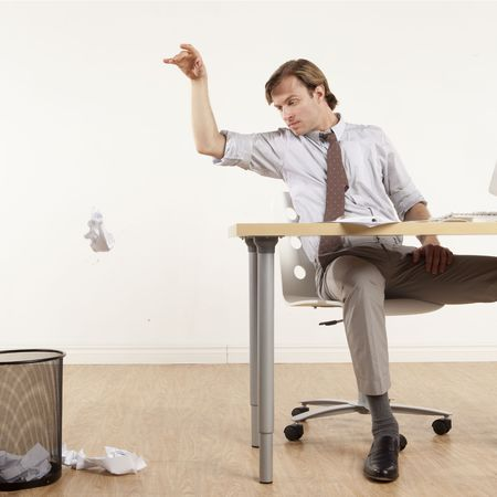 professional man sitting at desk throwing papers in wastebasket