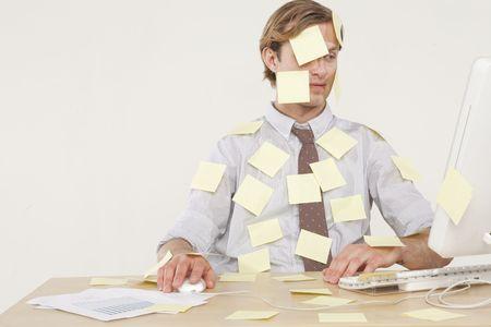 oficina desordenada: profesional hombre sentado en un escritorio cubierto de notas de recordatorio amarillo