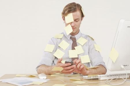 profesional hombre sentado en un escritorio cubierto de notas de recordatorio amarillo