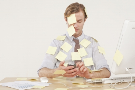 professional man sitting at desk covered in yellow reminder notes
