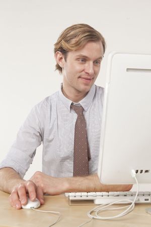 professional man sitting at computer with pleasant expression  Stock Photo