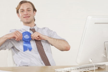 incentives: professional man sitting at desk with award ribbon  Stock Photo