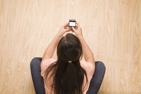 overhead shot of woman using a mobile device Stock Photo - 5123340