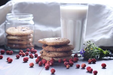 American chocolate chip cookies on a table and in a glass jar stacked on top of each other. Cookies, a glass of milk, strawberries, flowers and a linen towel. Rural still life.