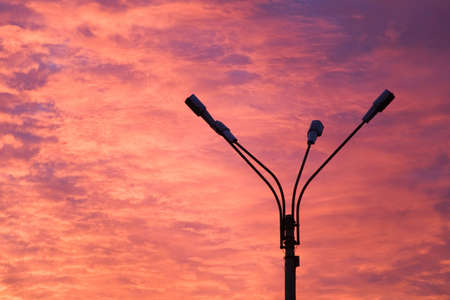 incarnadine: the threatening flame-colored sunset and silhouette of lamppost Stock Photo