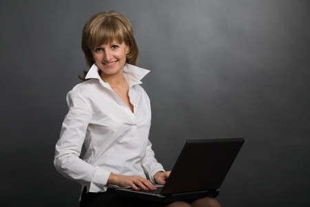 blusa: la mujer atractiva joven con la computadora port�til negra