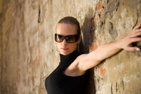 the young attractive woman standing at brick wall photo