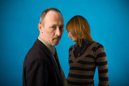 senior man and young woman on blue background