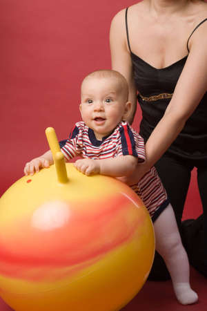 the little boy with ball on red background