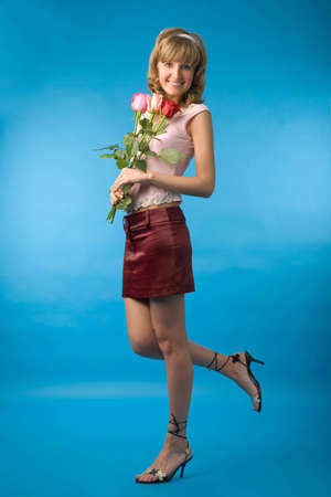 the young woman with flowers on blue background photo