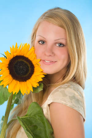 the young woman with sunflower on blue background photo