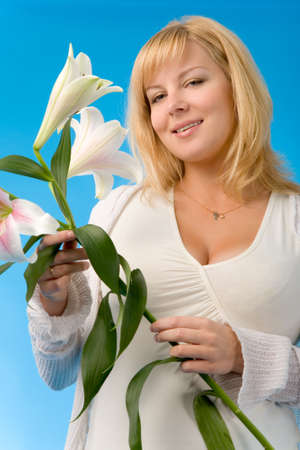 the pregnant woman with madonna lily on blue background photo