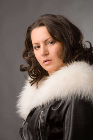 young woman in fur coat on grey background photo