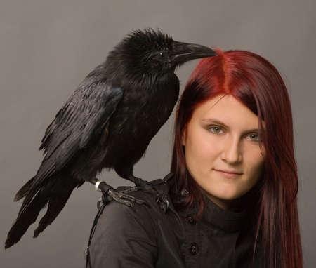 harridan: Joven mujer con cuervo negro sobre fondo gris