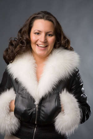 young woman in fur coat on gray background photo