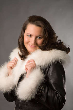 sheepskin: young woman in fur coat on gray background