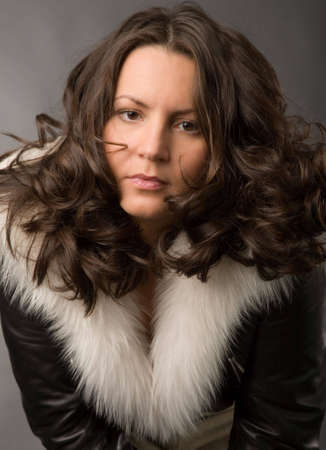 serious young woman in fur coat on gray background photo