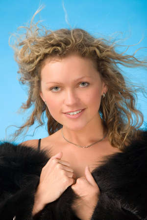 flyaway: portrait of young woman in fur coat with fly-away hair