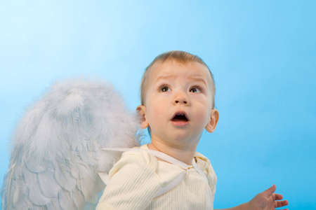 amazed boy dressed as Cupid on blue background photo