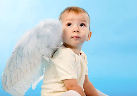 small boy dressed as Cupid on blue background photo