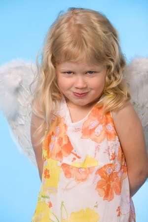 kleines Mädchen dreessed als Engel auf blauem Hintergrund