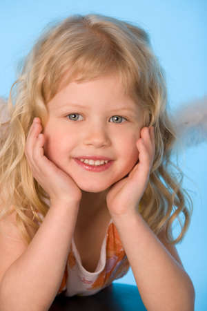small girl dreessed as angel on blue background