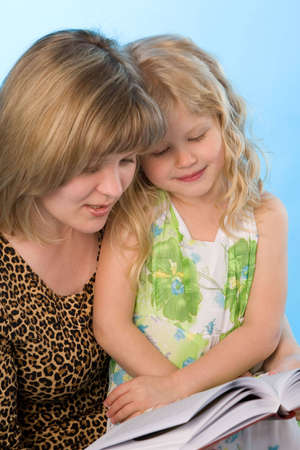 mother with daughter reading a book on a blue background photo