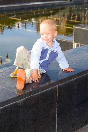 parapet: The little boy sits on a marble parapet