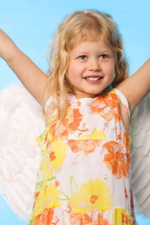 small girl dreessed as angel on blue background photo