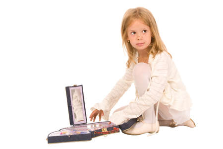 The little girl plays with a cosmetics set photo