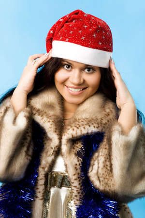 young woman in fur coat with christmas cap photo