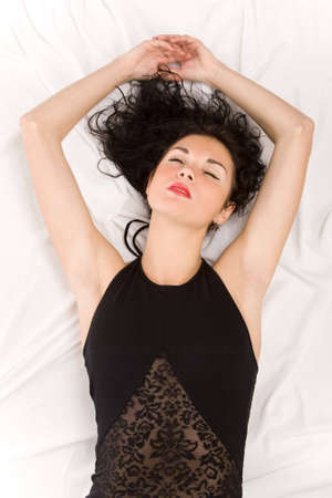 bedsheet: The beautiful woman lies on a white bed-sheet