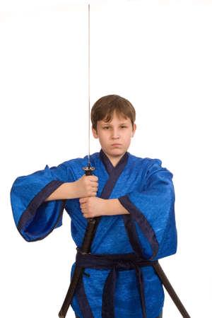 imminence: teen boy in blue kimono with sword Stock Photo