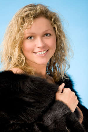 closeup portrait of a young blond curly-headed woman in fur on a blue background photo