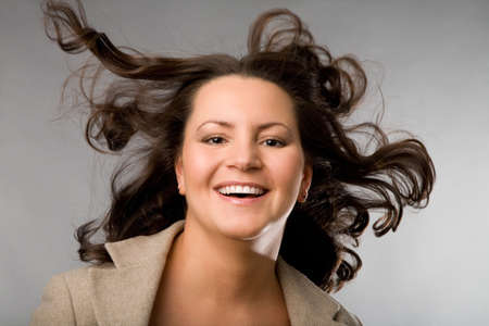 flying hair: closeup portrait of the laughing woman with flying hair on grey background