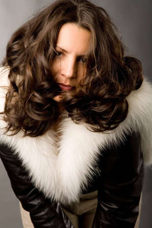 closeup portrait of the brunette curly-headed woman in fur on grey background photo