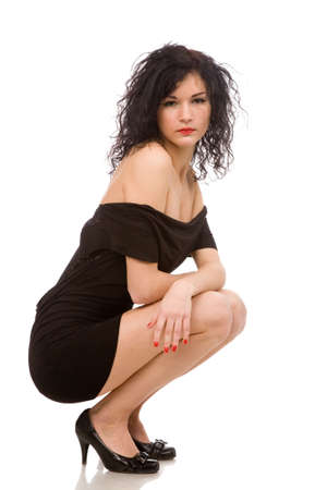 portrait of the young brunette woman in the squatting position on a white background photo